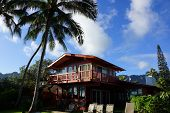 stock photo of lawn chair  - Red Two Story Beach House with tall coconut trees lawn chairs and mountains in the background on Oahu Hawaii on a beautiful day - JPG