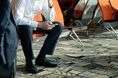 foto of work bench  - Businessman sitting at airport terminal using smartphone - JPG
