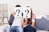 pic of punctuation marks  - Couple in the living room with question marks in front of their faces - JPG