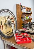 Wheels and bicycle parts over workshop table