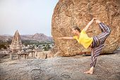 stock photo of natarajasana  - Woman doing yoga dancer pose near Virupaksha temple in Hampi Karnataka India - JPG