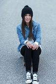 Young Brunette Skateboarder Girl Sitting On Skateboard