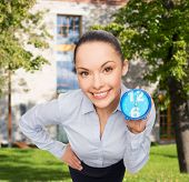 business, time and deadline concept - smiling businesswoman with blue clock