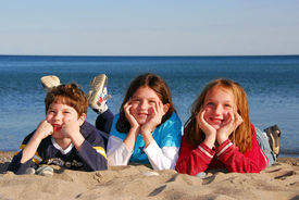 picture of children beach  - Three children lying on a beach laughing - JPG