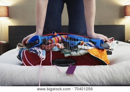 Low section of woman kneeling on overstuffed suitcase in bed