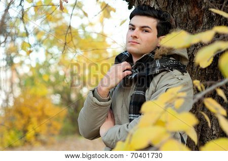 Young stylish man portrait dressed in a jacket and plaid scarf relaxing in autumn park.