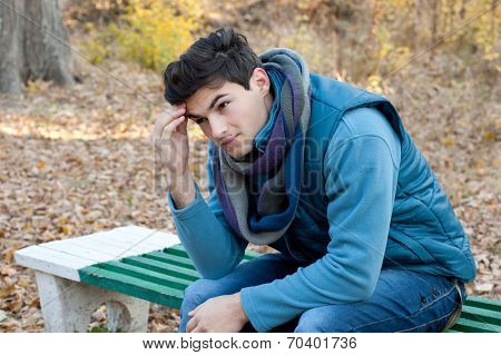 Portrait of young frustrated man thinking about the problems, autumn outdoor.
