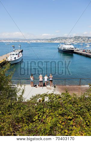 A group of young blonde girls waiting for their ferry on the dock. Ile Sainte-Marguerite (Larins Islands) - Cannes, French Riviera, Europe.