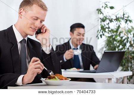 Busy Businessmen Eating Lunch In Office