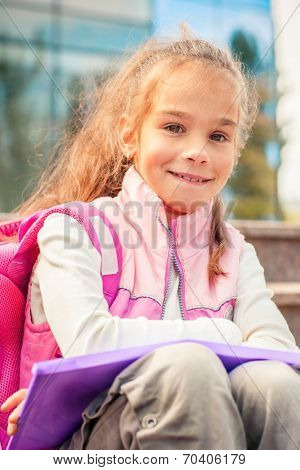 Portrait of a cheerful primary school student after study
