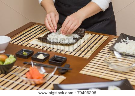 Hands of woman chef filling japanese sushi rolls with rice