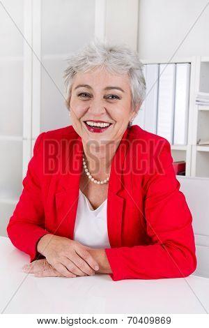 Attractive Older Senior Businesswoman Sitting At Desk Wearing Red Jacket.