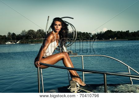 beautiful young woman sit on fishing boat at sea full body shot