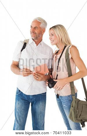 Happy tourist couple using the guidebook on white background