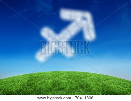 Cloud in shape of sagittarius star sign against green hill under blue sky