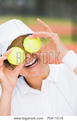 Pretty tennis player holding balls over her eyes on a sunny day
