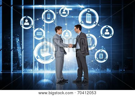 Businessmen shaking hands against hologram interface in office overlooking city