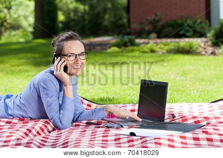 Woman Working On Laptop In Garden