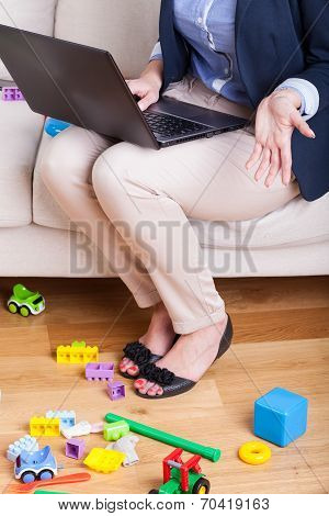 Mother Working On Laptop At Home