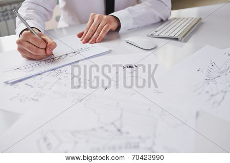 Businessman drawing sketches at workplace