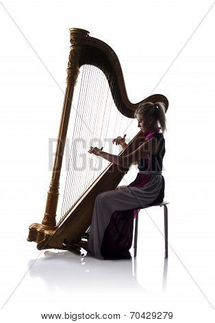 Silhouette of woman with harp