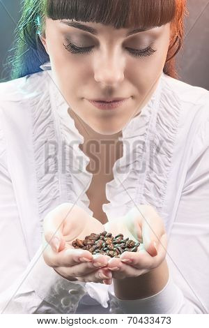 Portrait Of Young Caucasian Girl Holding Heap Of Unbroken Coffee Beans And Breathing In Aroma