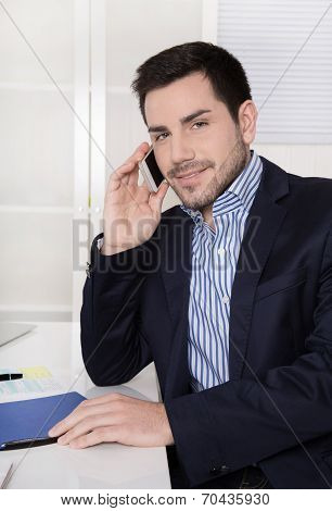 Handsome Businessman Sitting At Desk Talking On Mobile.