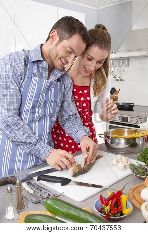 Young Fresh Married Couple In The Kitchen Cooking Together Fresh Fish.