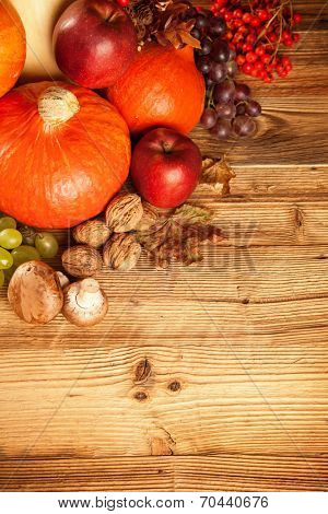 Autumn concept shot from top. Mix of pumpkins, fruit and vegetable on wooden table.