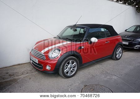 VALENCIA, SPAIN - AUGUST 20, 2014: Mini Cooper car parked in the street in Valencia, Spain.  In 1999 the Mini was voted the second most influential car of the 20th century, behind the Ford Model T.