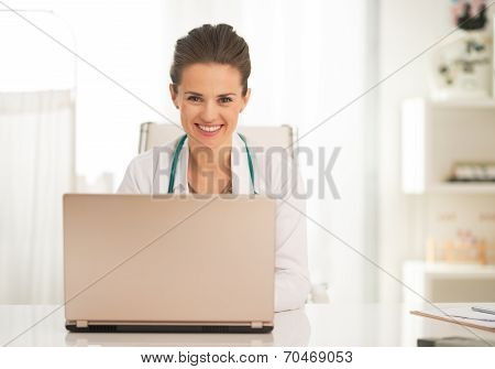 Happy Doctor Woman Working On Laptop In Office