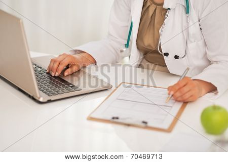 Closeup On Doctor Woman Working On Laptop In Office