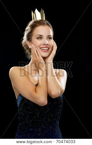 people, holidays, royalty and glamour concept - laughing woman in evening dress wearing golden crown over black background