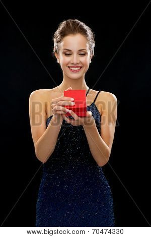 holidays, presents, luxury and happiness concept - smiling woman in dress holding red gift box over black background