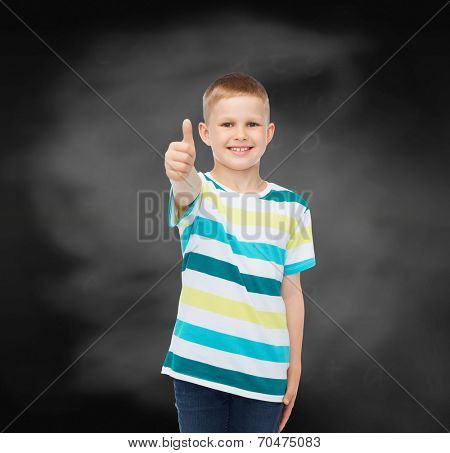 happiness, childhood, school, education and people concept - smiling little boy showing thumbs up over blackboard background
