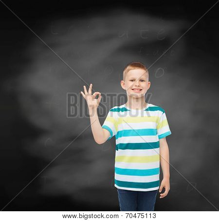 childhood, gesture, education and people concept - smiling little boy in casual clothes making ok gesture over blackboard background