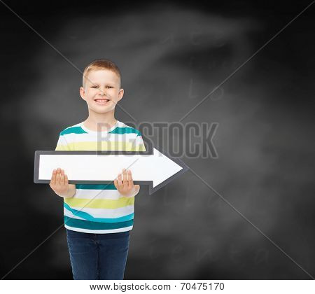 advertising, direction, education and childhood concept - smiling little boy with white blank arrow over black chalk board background