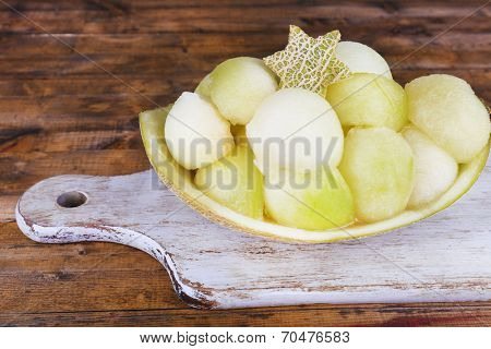 Melon in melon peel on cutting board on wooden background