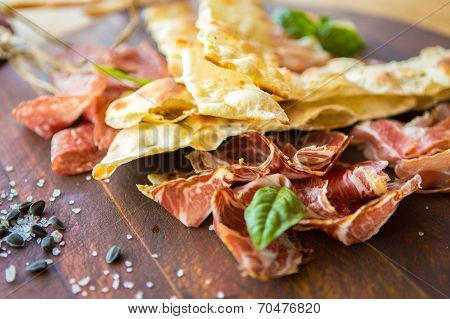 Homemade prosciutto and basil on a wooden board