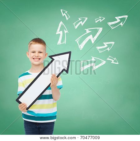 advertising, direction, education and childhood concept - smiling little boy with white blank arrow pointing up over green board with doodles background