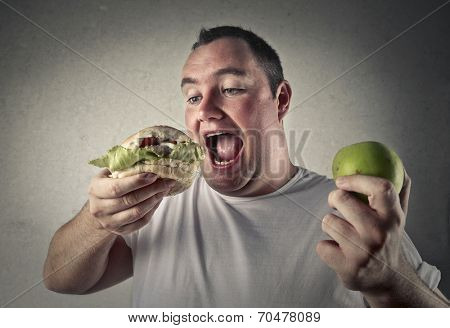 fat man deciding whether to eat a healthy apple or more appetizing junk food