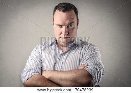 angry businessman looking in front of his eyes with his arms folded
