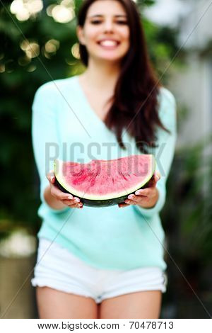 Beautiful woman holding fresh watermelon. Focus on watermelon