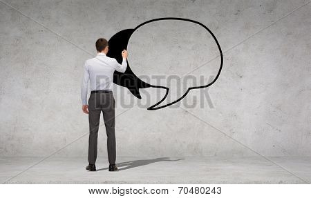 business and office people concept - businessman or teacher with marker drawing text bubble over concrete wall background from back