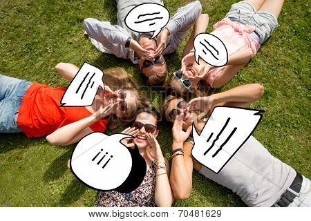 friendship, leisure, summer, message and people concept - group of smiling friends lying with text bubble doodles in circle on grass outdoors