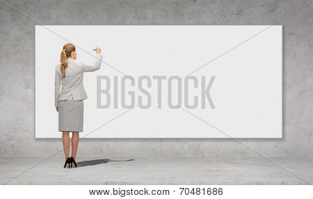 business, education and office people concept - businesswoman or teacher with marker writing or drawing something on white blank board over concrete wall background from back