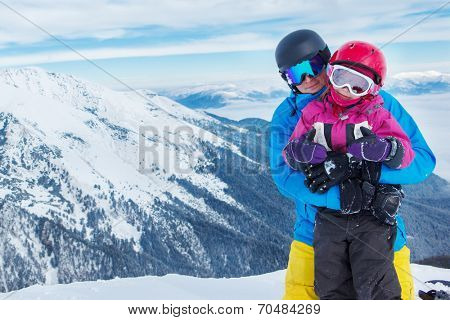Father and daughter with ski helmets on, in winter mountains