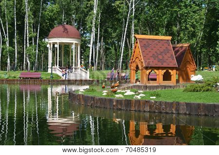 KHARKOV, UKRAINE - JUNE 10, 2014: People resting at the pond in the Central park named after M. Gorky. The park was found in 1893, and completely reconstructed in 2011-2012