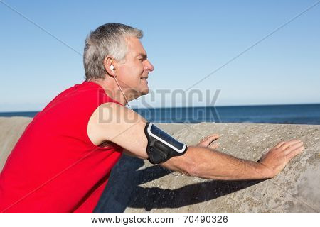 Active senior man stretching before a jog on a sunny day