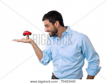 Young Happy Attractive Man With Toy Car On Top Of Coins Pile Isolated